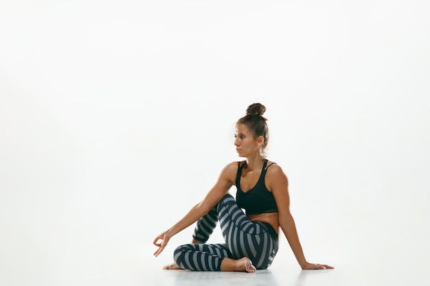 Jovem desportiva fazendo prática de ioga isolada no fundo branco do estúdio. ajuste o modelo feminino flexível praticando. conceito de estilo de vida saudável e equilíbrio natural entre o desenvolvimento corporal e mental.