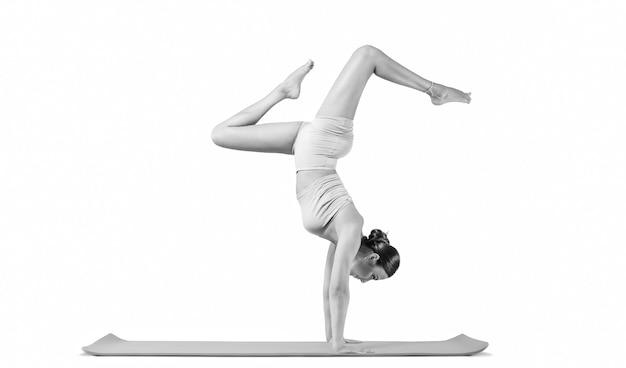 Jovem desportiva fazendo prática de ioga. isolado em um fundo branco. o conceito de estilo de vida saudável e equilíbrio natural entre o desenvolvimento corporal e mental. pilates, alongamento. Foto Premium