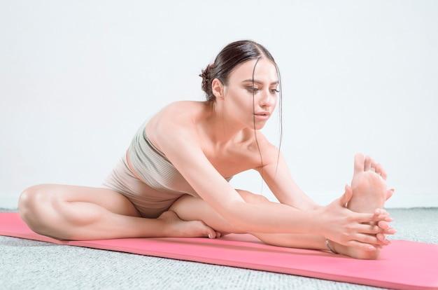 Jovem desportiva fazendo prática de ioga. o conceito de estilo de vida saudável e equilíbrio natural entre corpo e mente. pilates, alongamento. mídia mista Foto Premium