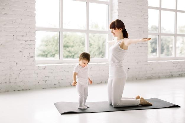 Jovem desportiva mãe e bebê menina vestindo branco malhando na esteira, exercitando juntos, pai e filho desenvolvimento saudável, jogo, fitness e relaxamento