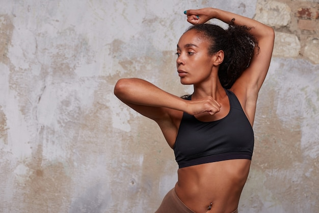 Jovem desportiva, morena, cacheada, vestindo uma blusa preta atlética fazendo elemento de dança e olhando para o lado com uma cara séria