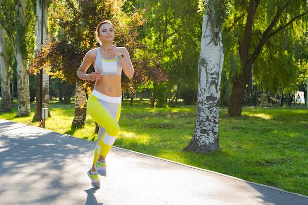 Jovem desportiva no sportswear correndo no parque de manhã