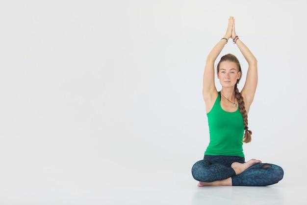 Jovem desportiva praticando ioga isolada no fundo branco - conceito de vida saudável e equilíbrio natural entre o corpo e o desenvolvimento mental