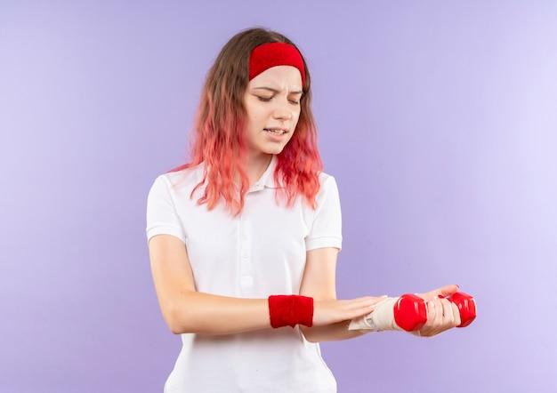 Jovem desportiva segurando dois halteres, fazendo exercícios olhando para o pulso enfaixado, sentindo dor em pé sobre a parede roxa