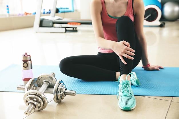 Jovem desportiva sentada no chão no ginásio