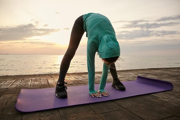 Jovem desportiva usa roupas esportivas brilhantes, faz alongamento matinal no tapete de ioga roxo, treina à beira-mar.