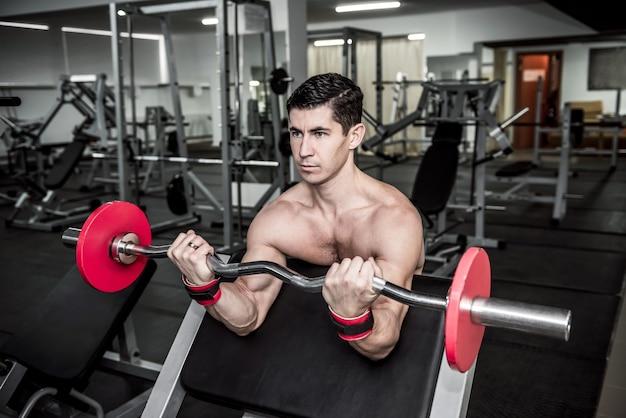 Jovem desportivo a trabalhar com halteres no ginásio Foto Premium