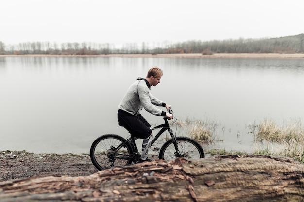 Jovem desportivo andando de bicicleta perto do lago
