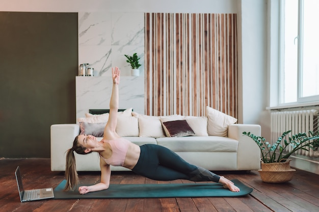 Jovem desportivo apto a fazer exercícios de prancha lateral e assistir o tutorial online no laptop na sala de estar.