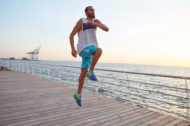 Jovem desportivo bonito barbudo saltando fazendo exercícios matinais à beira-mar, aquecimento antes de correr.