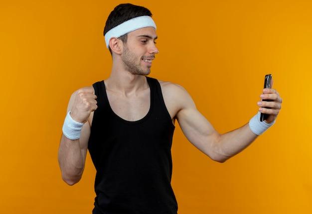 Jovem desportivo com a faixa na cabeça cerrando o punho fazendo selfie usando seu smartphone em pé sobre uma parede laranja