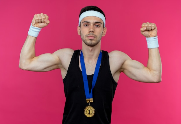 Jovem desportivo com fita para a cabeça e medalha de ouro ao redor do pescoço levantando o punho com expressão séria em pé sobre a parede rosa