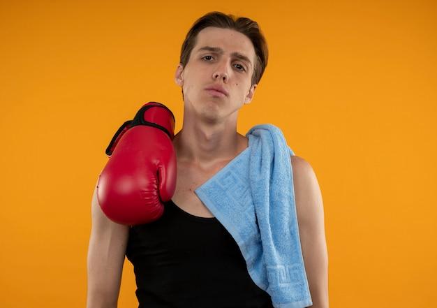 Jovem desportivo com toalha e luvas de boxe no ombro isolado na parede laranja