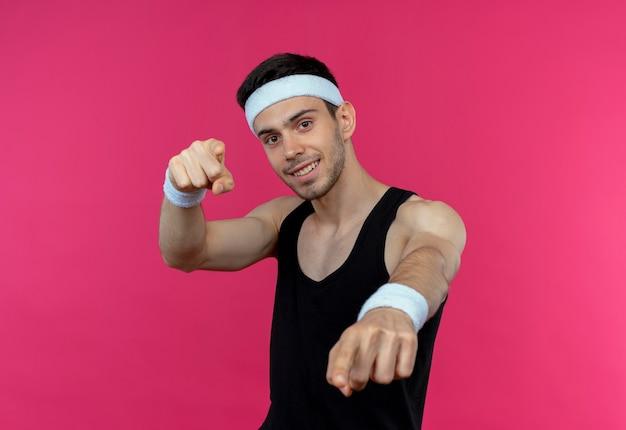 Jovem desportivo com uma bandana apontando com o dedo indicador para a câmera e sorrindo confiante sobre o rosa