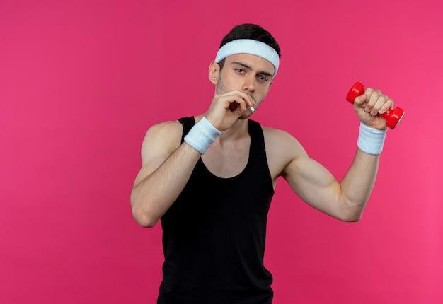 Jovem desportivo com uma bandana, malhando com halteres e fumando em pé sobre fundo rosa