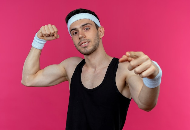 Jovem desportivo com uma bandana olhando para a câmera com expressão confiante, levantando o punho, mostrando o bíceps apontando com o dedo indicador para a câmera em pé sobre o fundo rosa