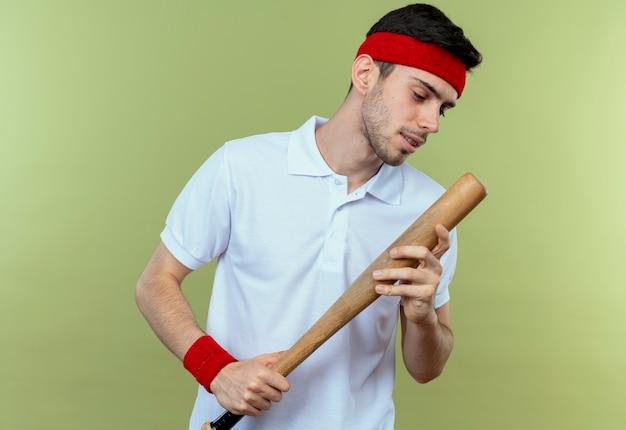 Jovem desportivo com uma bandana segurando um taco de beisebol olhando para ele de pé sobre um fundo verde