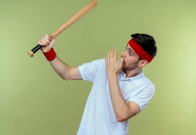 Jovem desportivo com uma bandana segurando um taco de beisebol olhando para ele espantado e surpreso em pé sobre um fundo verde