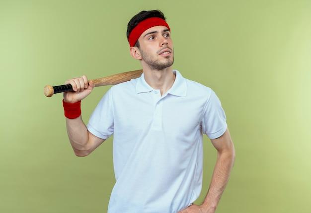 Jovem desportivo com uma bandana segurando um taco de beisebol, olhando para o lado com uma expressão pensativa em pé sobre um fundo verde