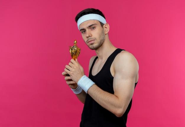 Jovem desportivo com uma bandana segurando um troféu e com uma expressão séria e confiante em pé sobre a parede rosa