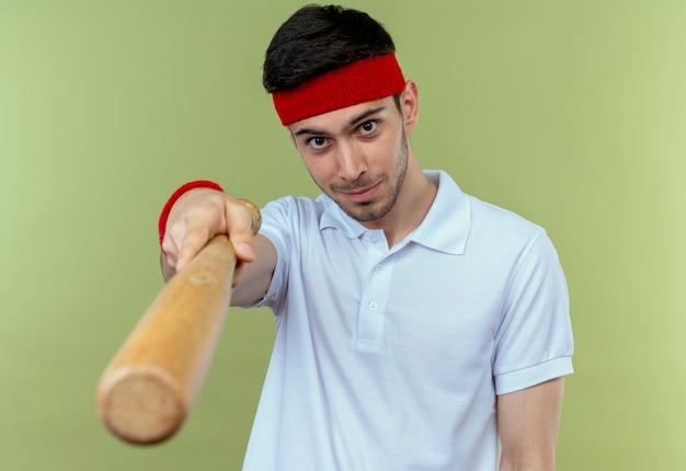 Jovem desportivo com uma faixa na cabeça a apontar com um taco de basebol para a câmara sobre o verde