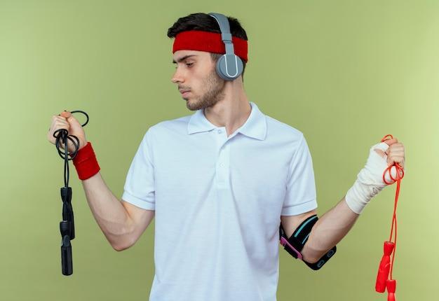Jovem desportivo com uma faixa na cabeça com fones de ouvido e uma pulseira de smartphone segurando cordas de pular, parecendo incerto sobre o verde