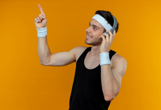 Jovem desportivo com uma faixa na cabeça e fone de ouvido, olhando para o lado apontando com o dedo para cima, sorrindo em pé sobre a parede laranja
