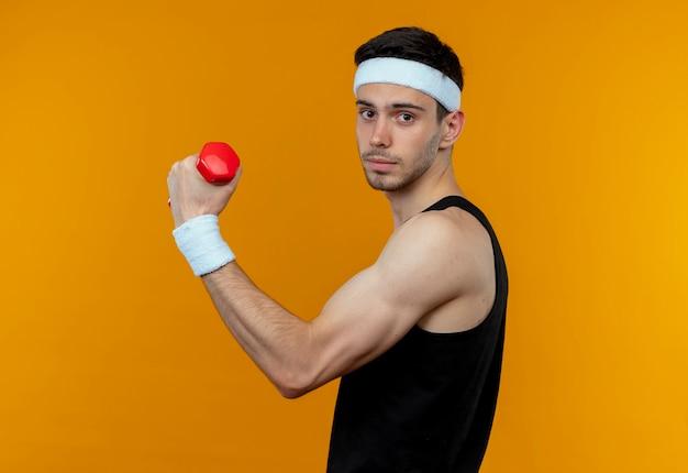 Jovem desportivo com uma faixa na cabeça, malhando com halteres, olhando para a câmera com uma cara séria em pé sobre um fundo laranja