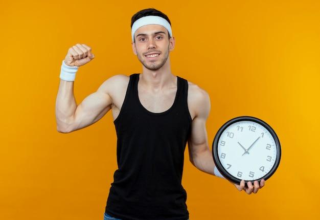 Jovem desportivo com uma faixa na cabeça, segurando o relógio de parede, cerrando os punhos, feliz e animado em pé sobre um fundo laranja