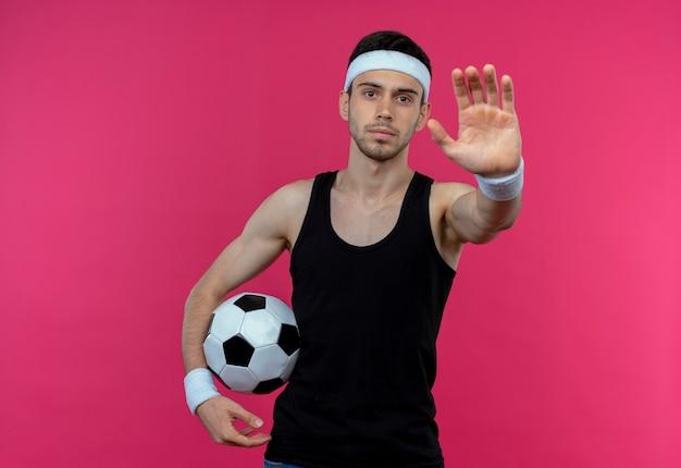 Jovem desportivo com uma faixa na cabeça, segurando uma bola de futebol, fazendo sinal de pare com a mão aberta e com uma cara séria em pé sobre a parede rosa