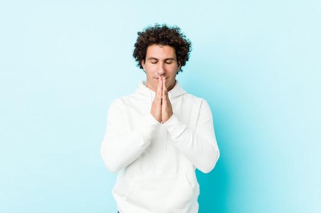 Jovem desportivo contra uma parede azul de mãos dadas perto da boca de oração, sentindo-se confiante