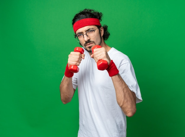 Jovem desportivo, de pé confiante na vista de perfil, usando uma faixa na cabeça e uma pulseira segurando halteres