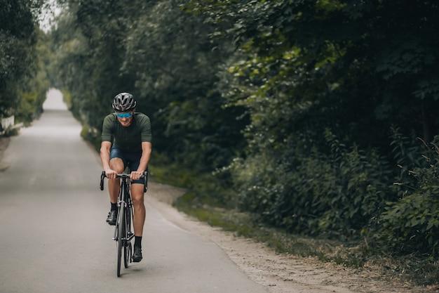 Jovem desportivo em activewear, capacete de segurança e óculos espelhados, andar de bicicleta na estrada. ciclista caucasiana com pernas musculosas, tendo treino duro e ativo no ar fresco.