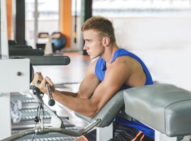 Jovem desportivo exercitando os bíceps no ginásio