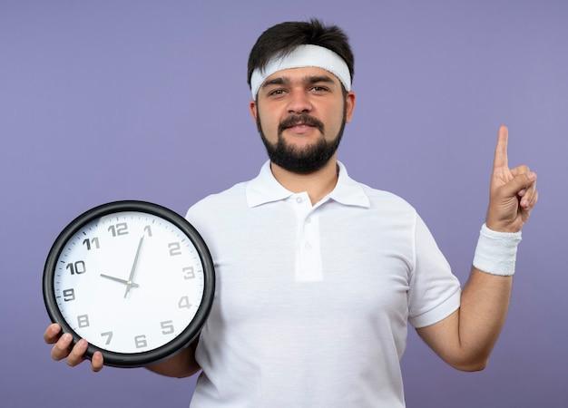 Jovem desportivo impressionado usando bandana e pulseira segurando o relógio de parede apontando para cima