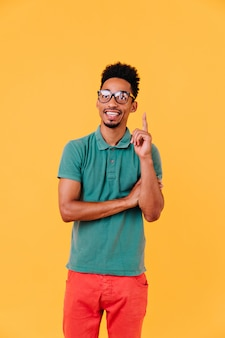Jovem desportivo posando de óculos. lindo modelo masculino em t-shirt verde sorrindo.