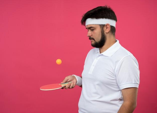 Jovem desportivo usando bandana e pulseira segurando uma raquete de pingue-pongue com bola isolada na parede rosa