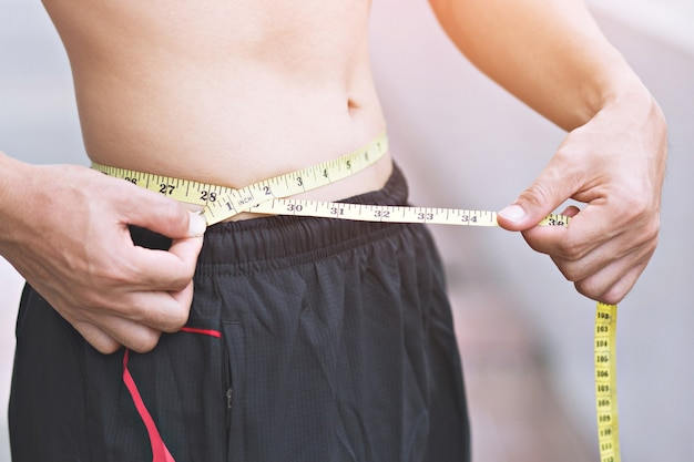 Jovem desportivo verifique o corpo com fita métrica ao ar livre. close up, conceito de saudável e esporte.