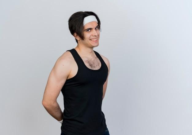 Jovem desportivo vestindo roupas esportivas e bandana, olhando para a frente, sorrindo maliciosamente de pé sobre uma parede branca
