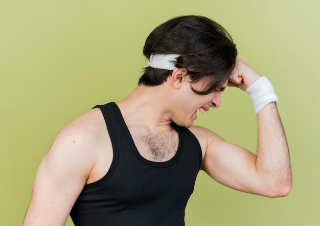 Jovem desportivo vestindo roupas esportivas e tiara levantando o punho e mostrando bíceps parecendo tensos