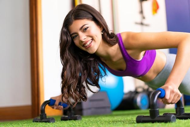 Jovem, desporto, mulher, em, um, ginásio, fazendo, push-ups