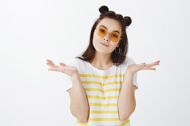 Jovem despreocupada posando com óculos de sol contra uma parede branca