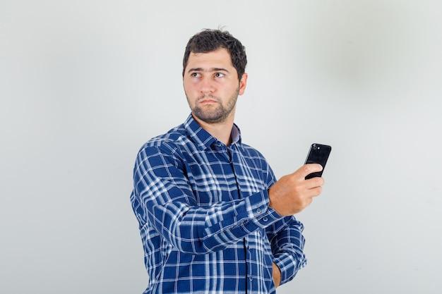 Jovem desviando o olhar com o smartphone na mão com uma camisa xadrez e parecendo descontente