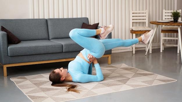 Jovem determinada mulher magro confiante fazendo exercícios em casa. o preparador físico treina em casa durante a quarentena. interior moderno claro