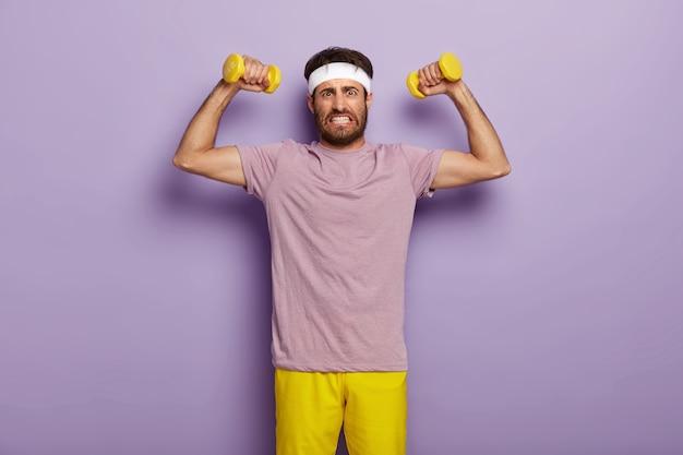Jovem determinado, desportivo, com a barba por fazer, aperta os dentes, levanta os braços musculosos, faz exercícios com halteres, aperta os dentes
