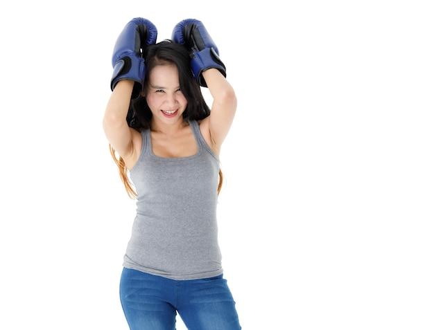 Jovem determinado em forma de mulher asiática com luvas de boxe azuis, em posição de combate e olhando para a câmera com um sorriso contra um fundo branco