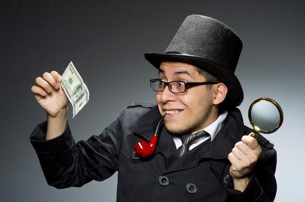Jovem detetive no casaco preto com dinheiro contra cinza