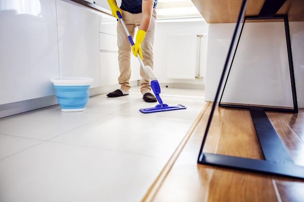 Jovem digno limpando o chão da cozinha e experimentando um novo produto de limpeza.