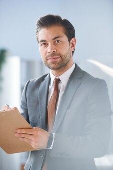Jovem diretor de sucesso de empresa de negócios olhando para você enquanto assina documento