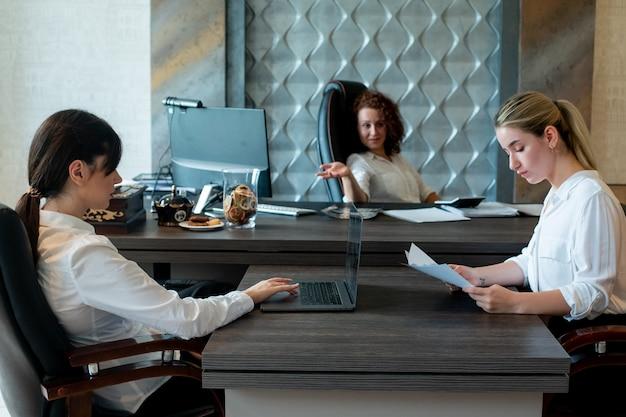 Jovem diretora de negócios sentada na mesa do escritório discutindo os resultados ou planejando o trabalho em uma reunião de grupo com colegas de trabalho trabalhando juntos no escritório